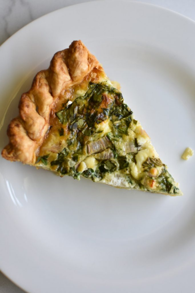 A slice of quiche florentine on a white plate