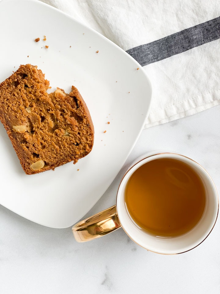 A slice of pumpkin apple bread with a bite out of it on a white plate with tea