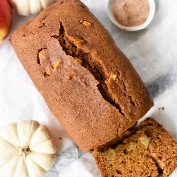 A loaf of pumpkin apple bread that's been sliced with pumpkins and cinnamon sugar
