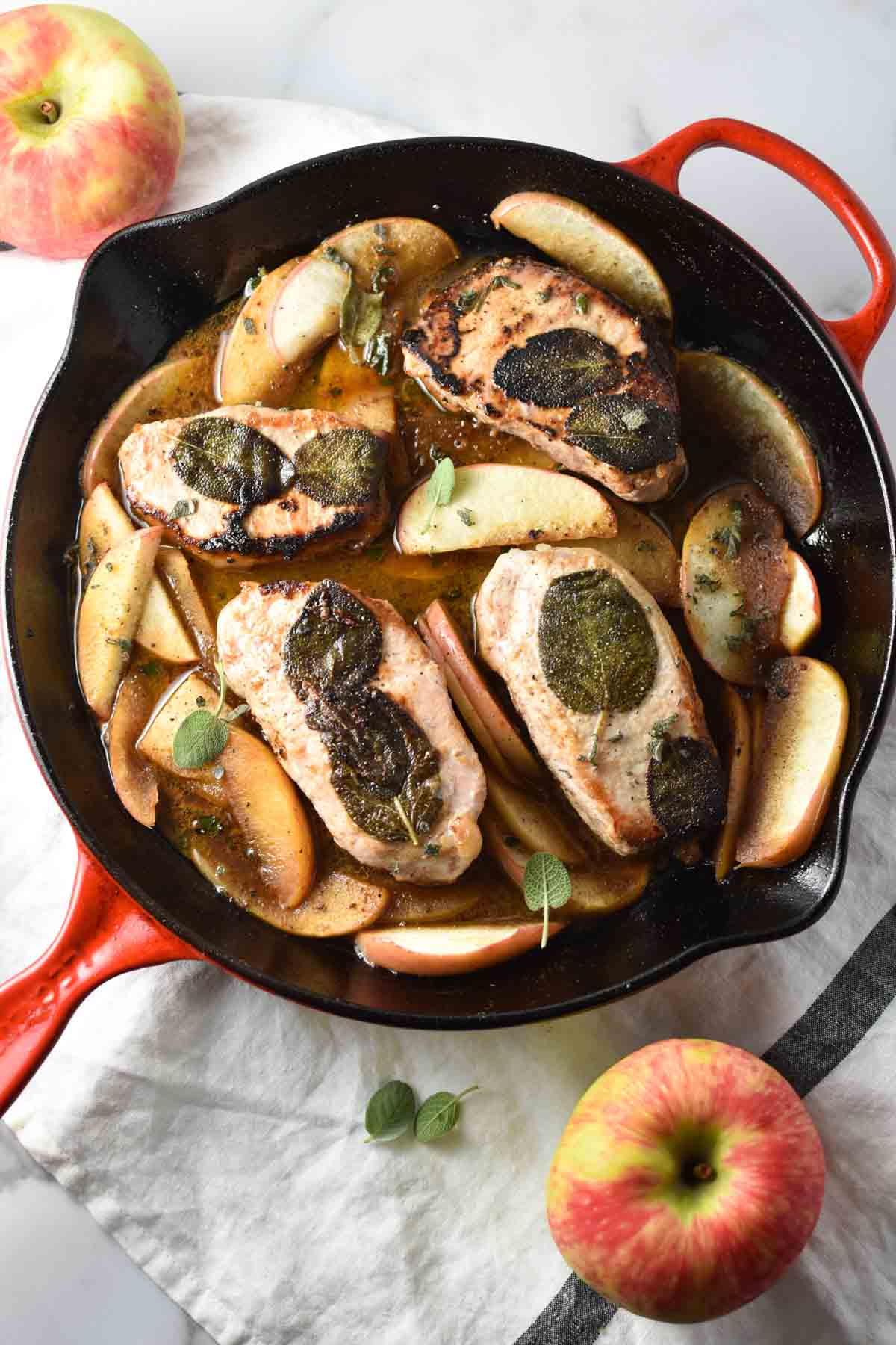 Pork chops with sage in a cast iron pan with apples and sauce