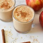 Two apple smoothies topped with cinnamon next to apples and cinnamon sticks