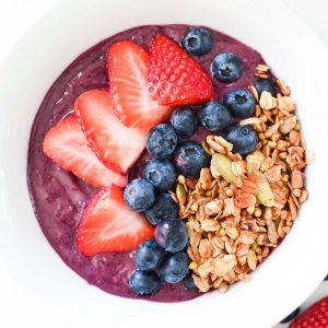 A purple acai bowl with strawberries, blueberries, and granola on top