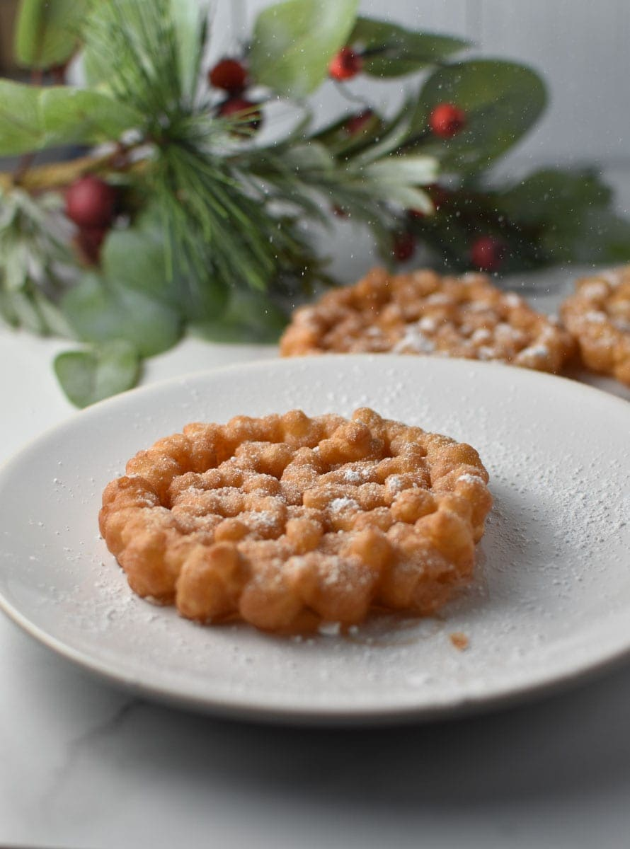 A cookie being dusted with powdered sugar