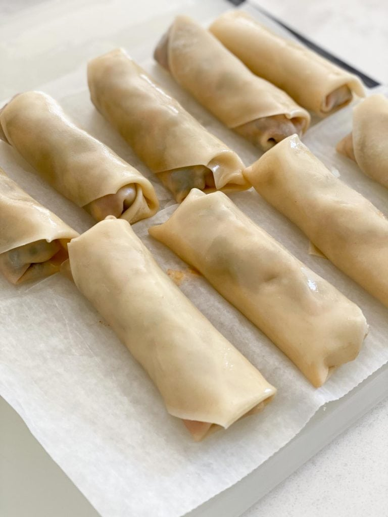 A line of uncooked egg rolls