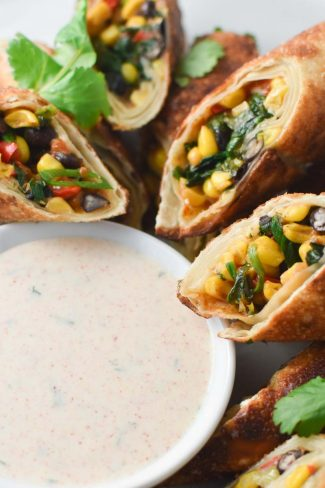 Air fried southwestern egg rolls on a plate with ranch dipping sauce and cilantro