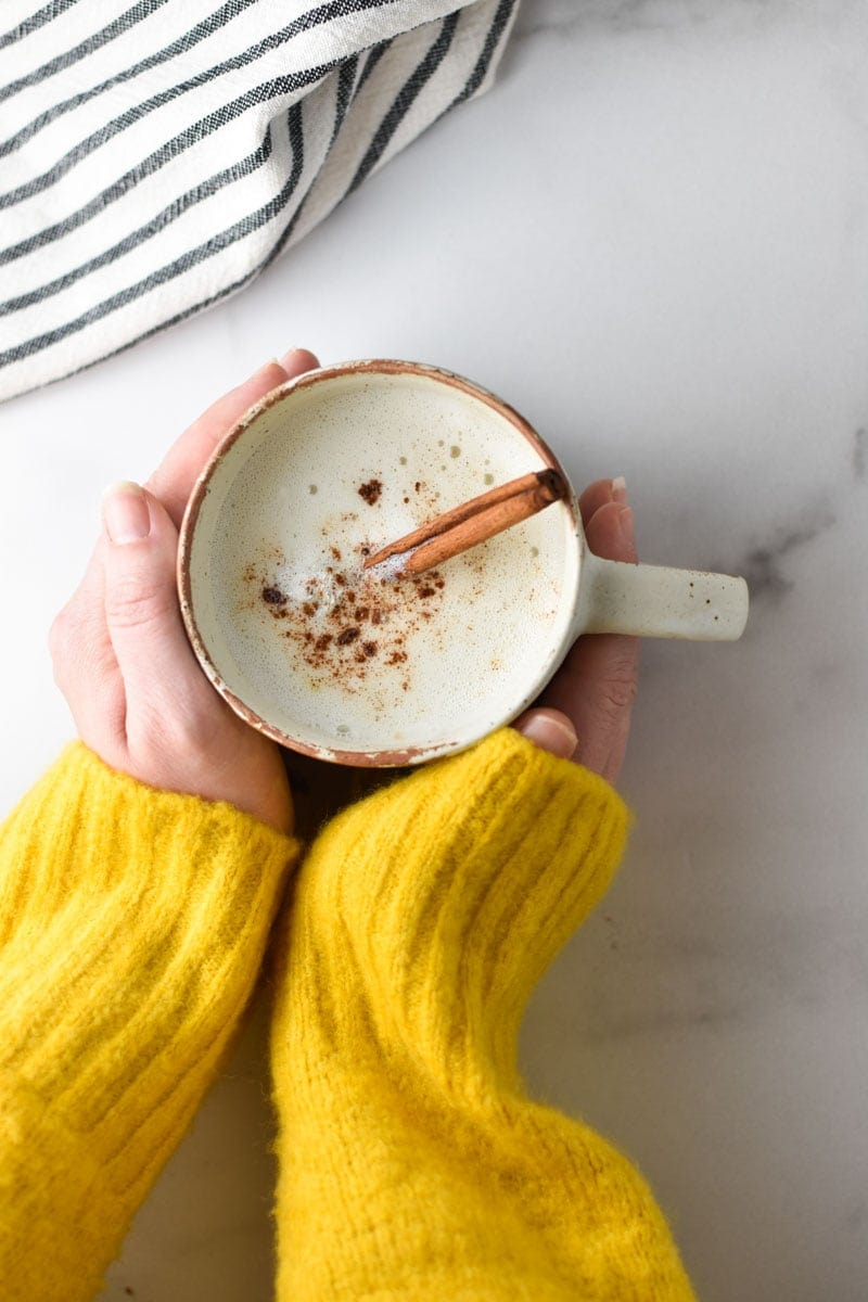 Two hands holding a cup of warm cinnamon milk
