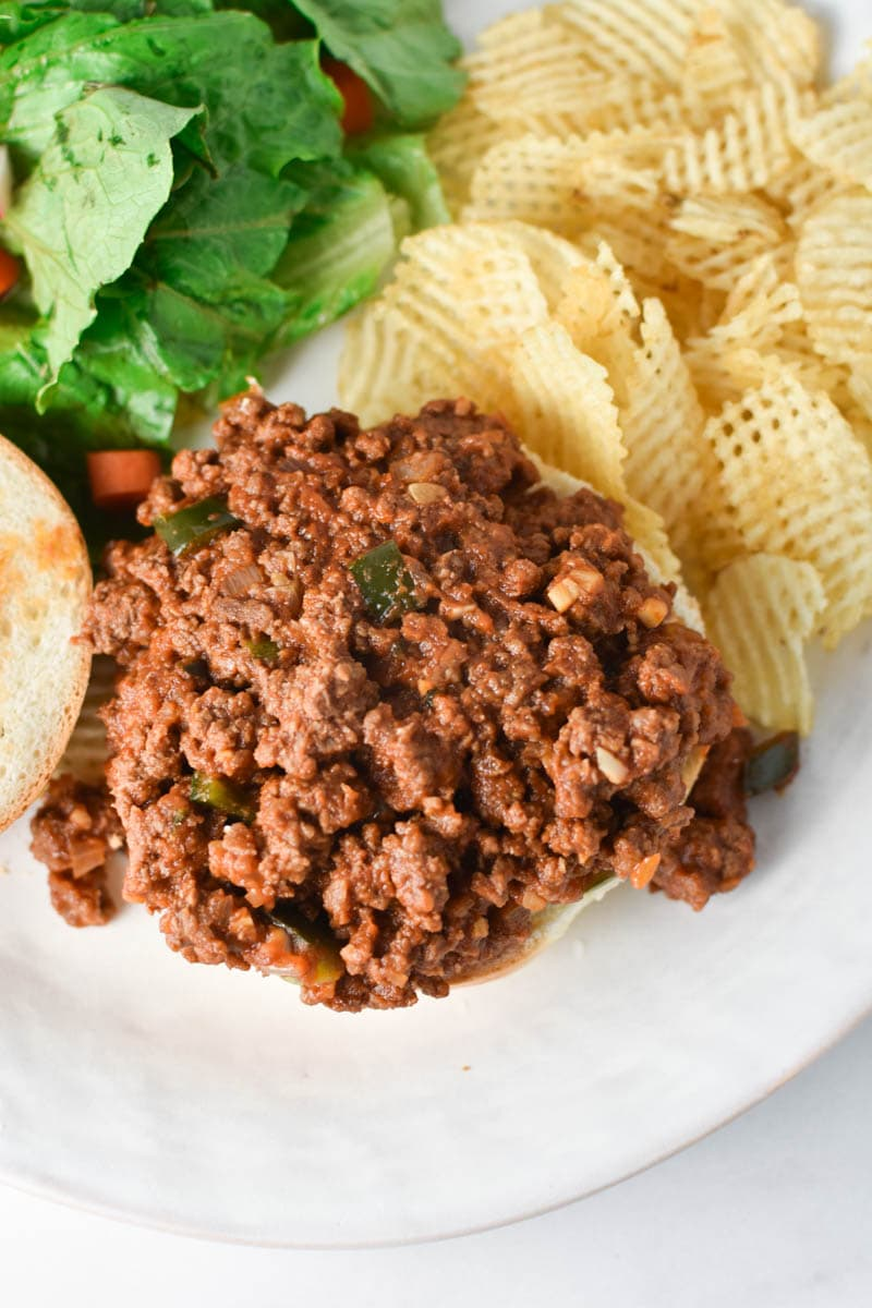 Sloppy joe filling without a bun next to potato chips and a salad