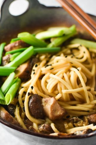 A gray bowl of mushroom ramen topped with green onion and sesame with chopsticks
