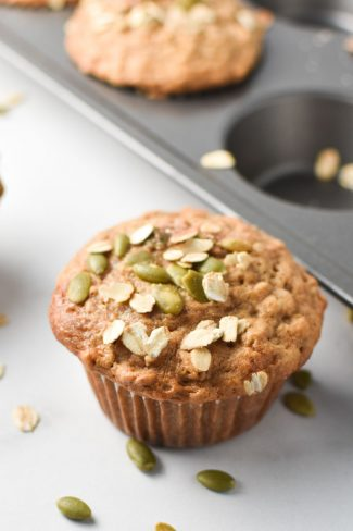 Cinnamon oatmeal muffins on a white table and in a baking pan, topped with oats and pumpkin seeds