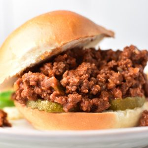 Sloppy joes without ketchup falling out of a bun on a white plate
