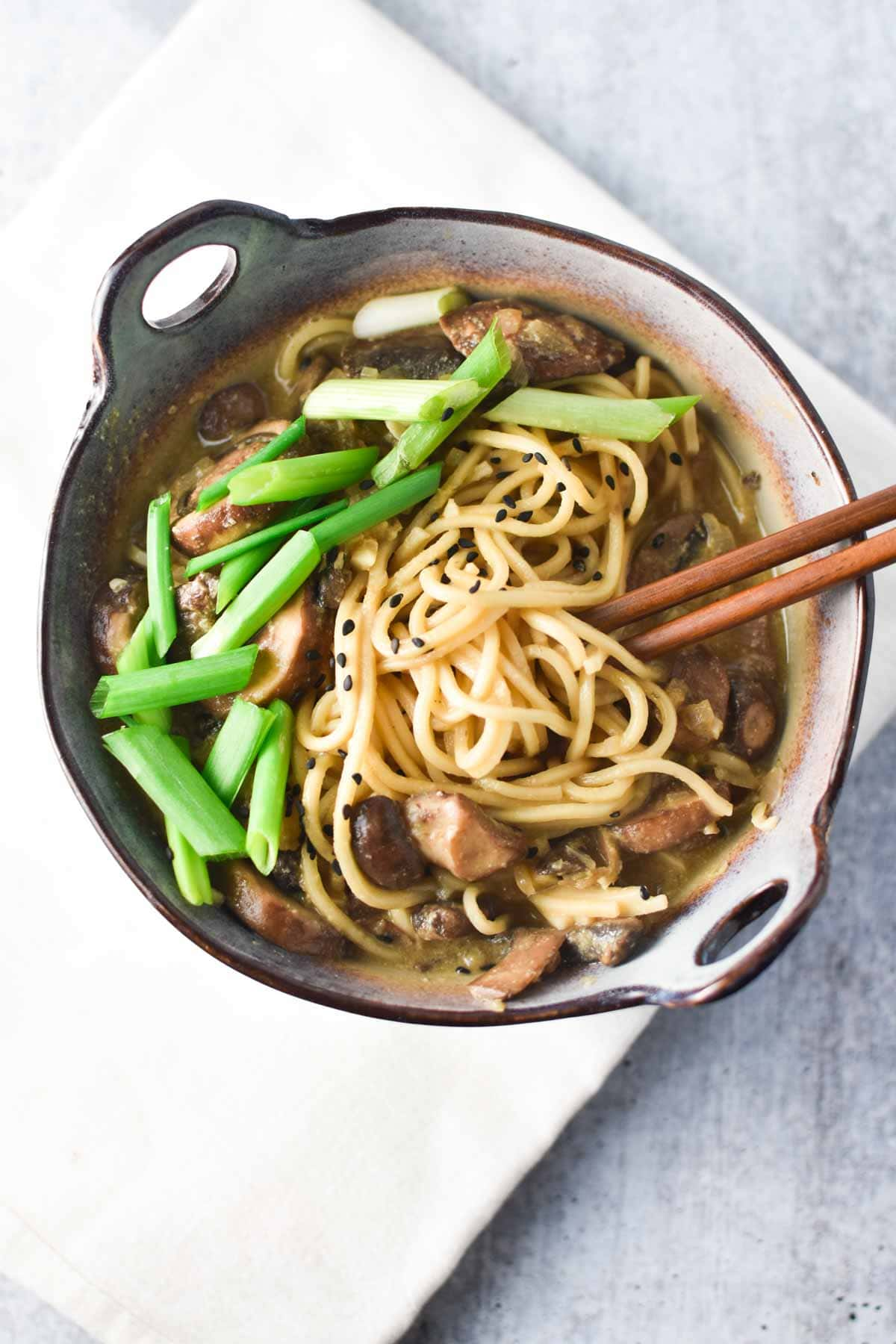 Vegan ramen in a bowl topped with scallions and mushrooms