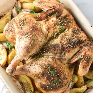 Zaatar roasted chicken on a bed of sumac potatoes and shallots in a roasting dish