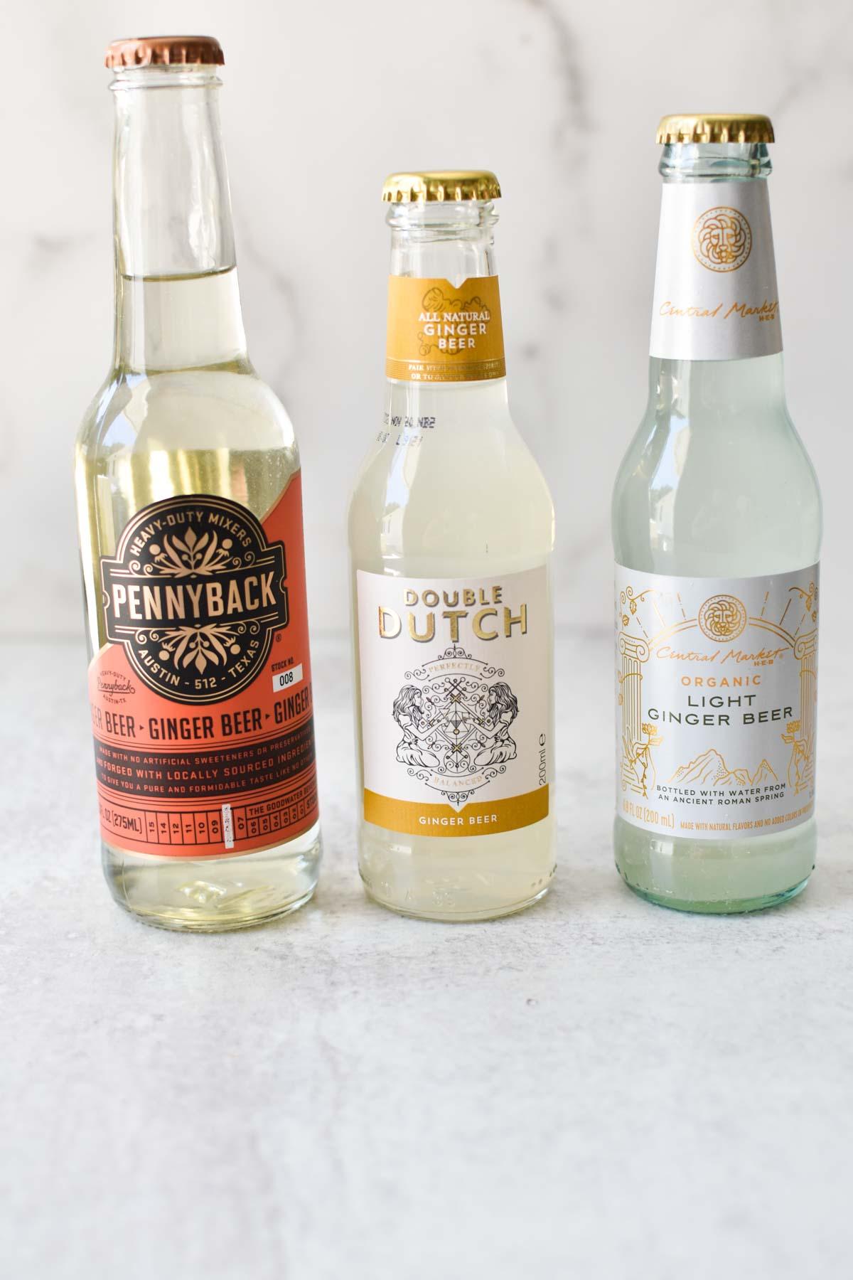 3 bottles of ginger beer on a white table