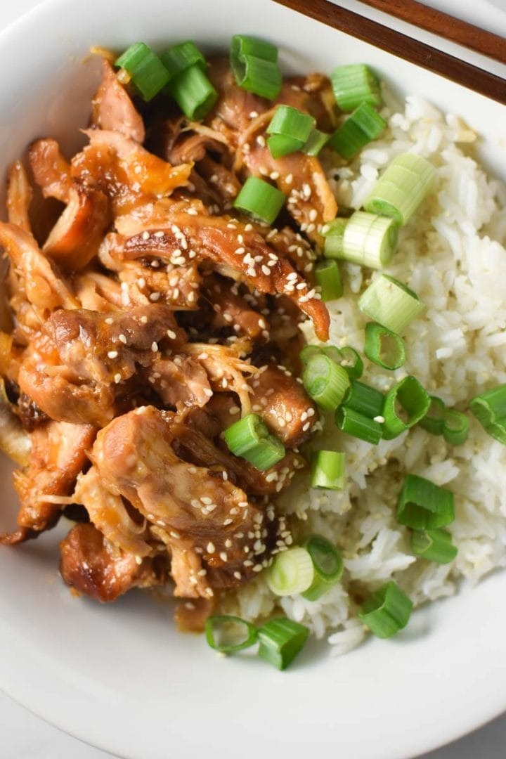 Shredded apricot chicken in a white bowl with white rice and sliced scallions on top