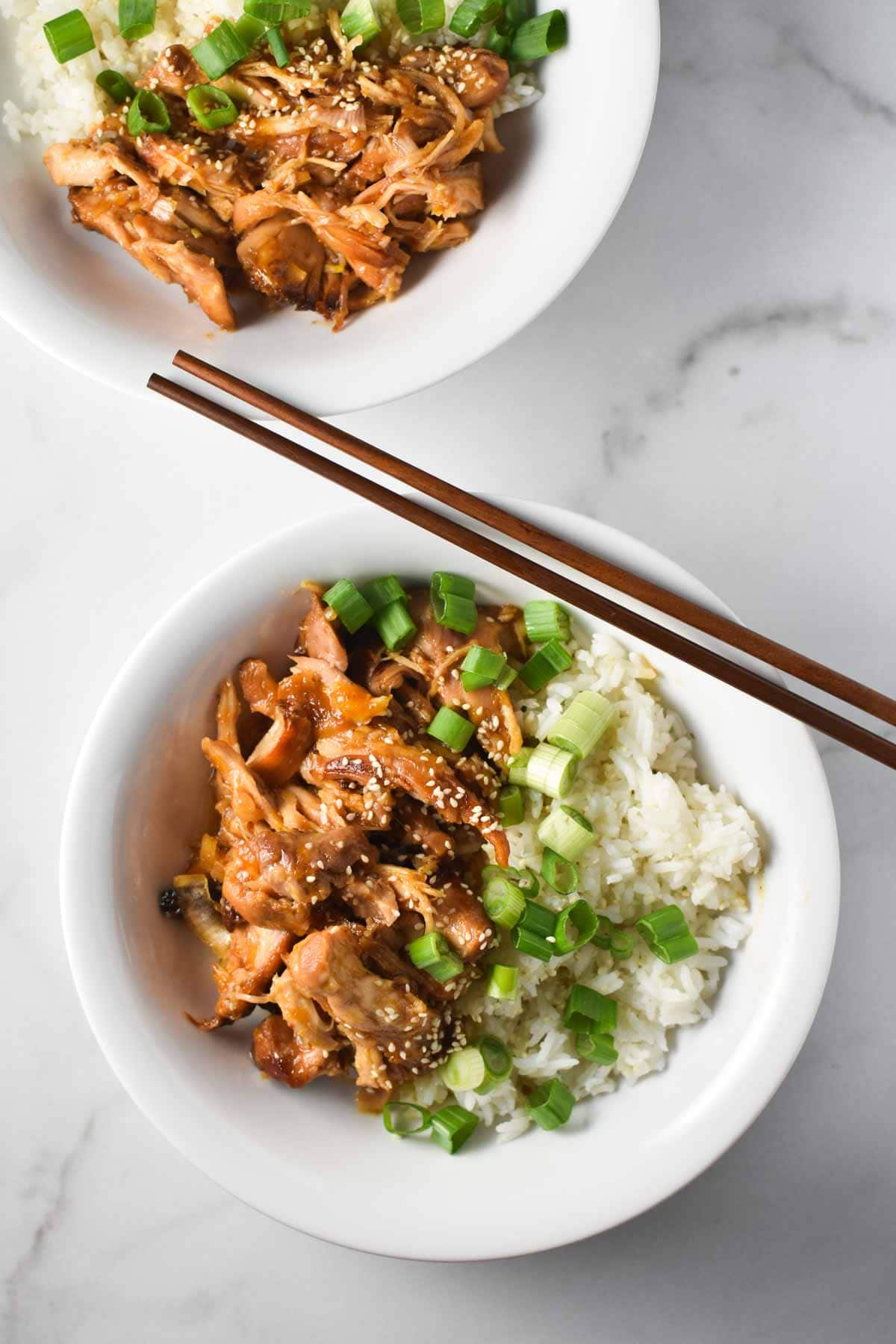 Two bowls of chicken in apricot sauce with rice and chopsticks laying on the side