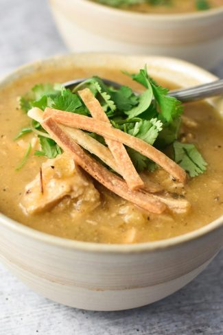 A bowl of green enchilada chicken soup topped with cilantro and tortilla strips with a spoon on a grey table