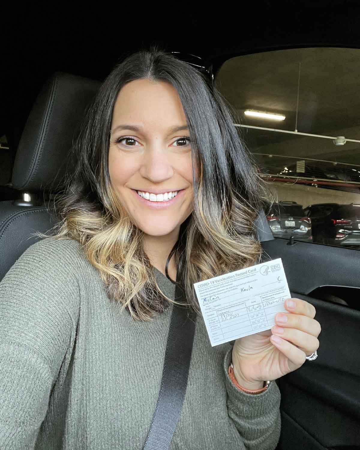 A woman smiling holding her vaccine card in the car