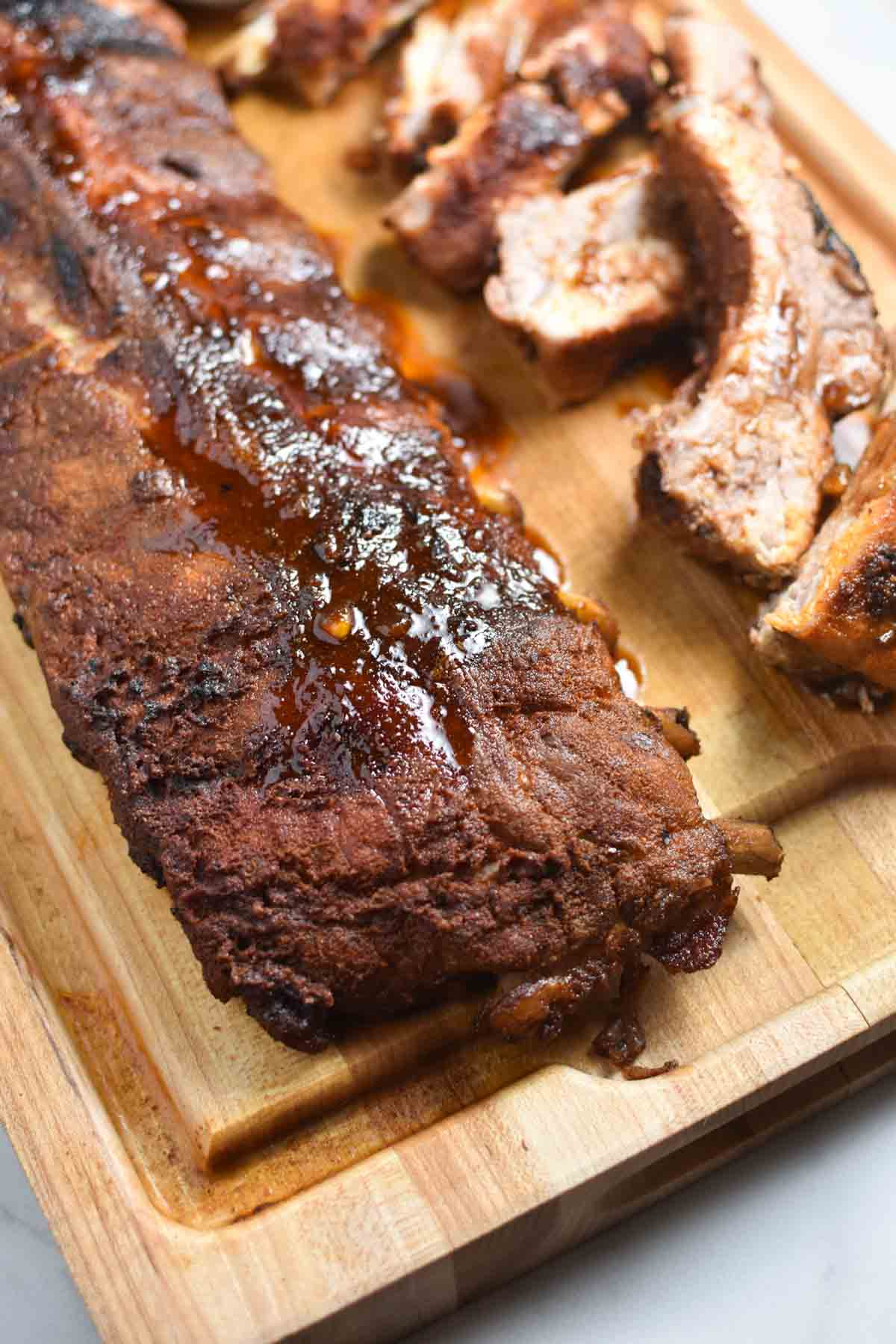 An unsliced rack of ribs with the dry rub and bbq sauce on top