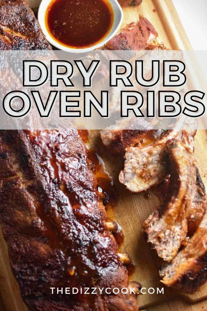 A whole rack of dry rubbed oven ribs next to sliced ribs and bbq sauce on a wooden board