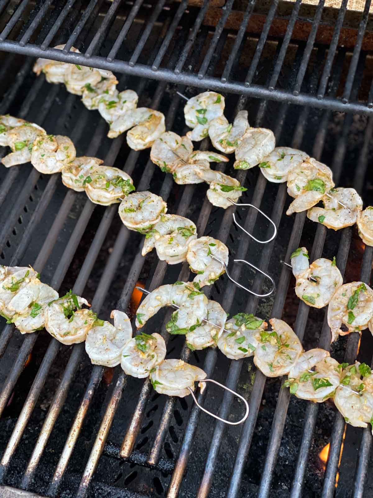 Raw shrimp on skewers on gas grill grates