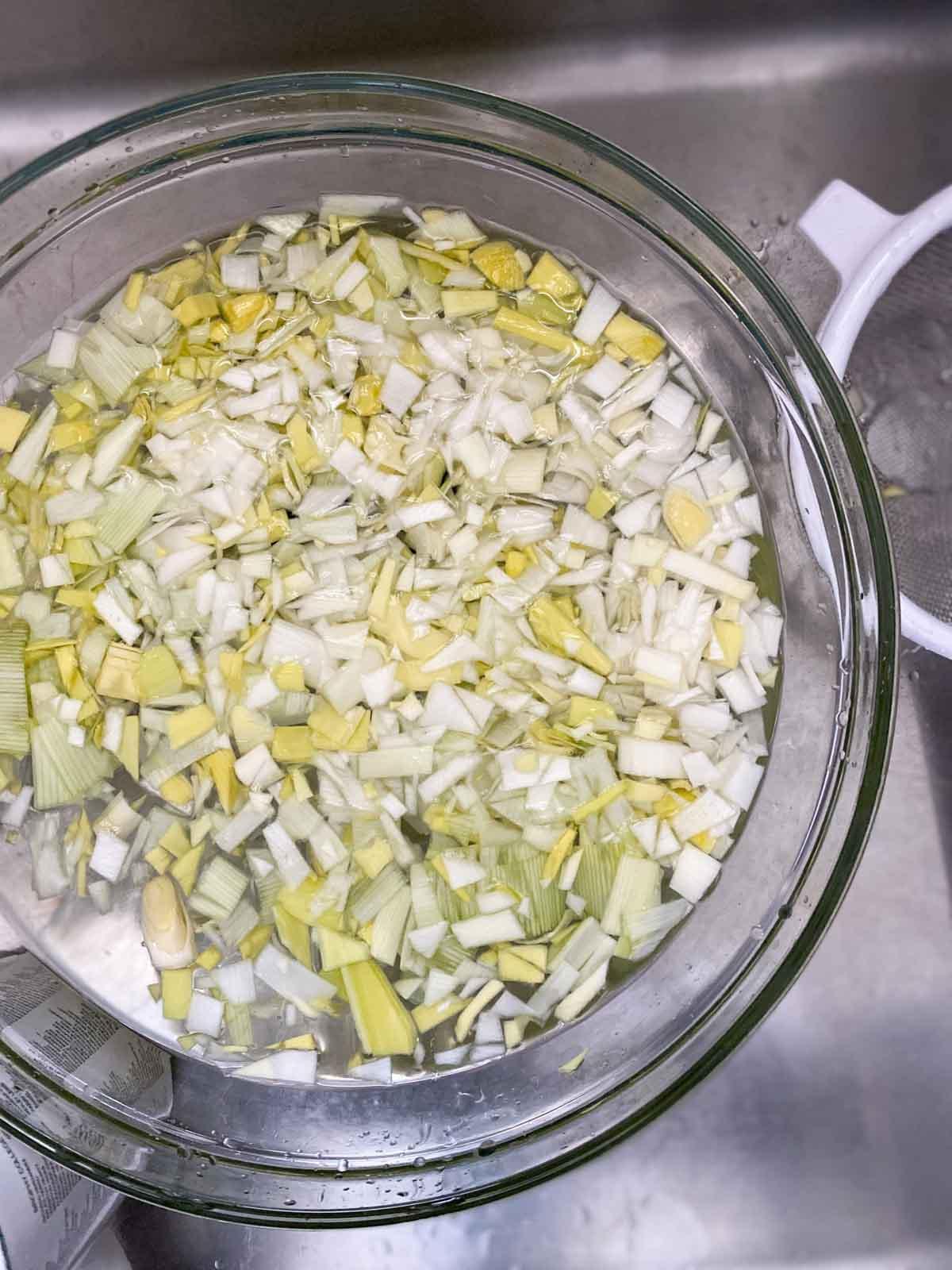 Leeks being washed in a colander