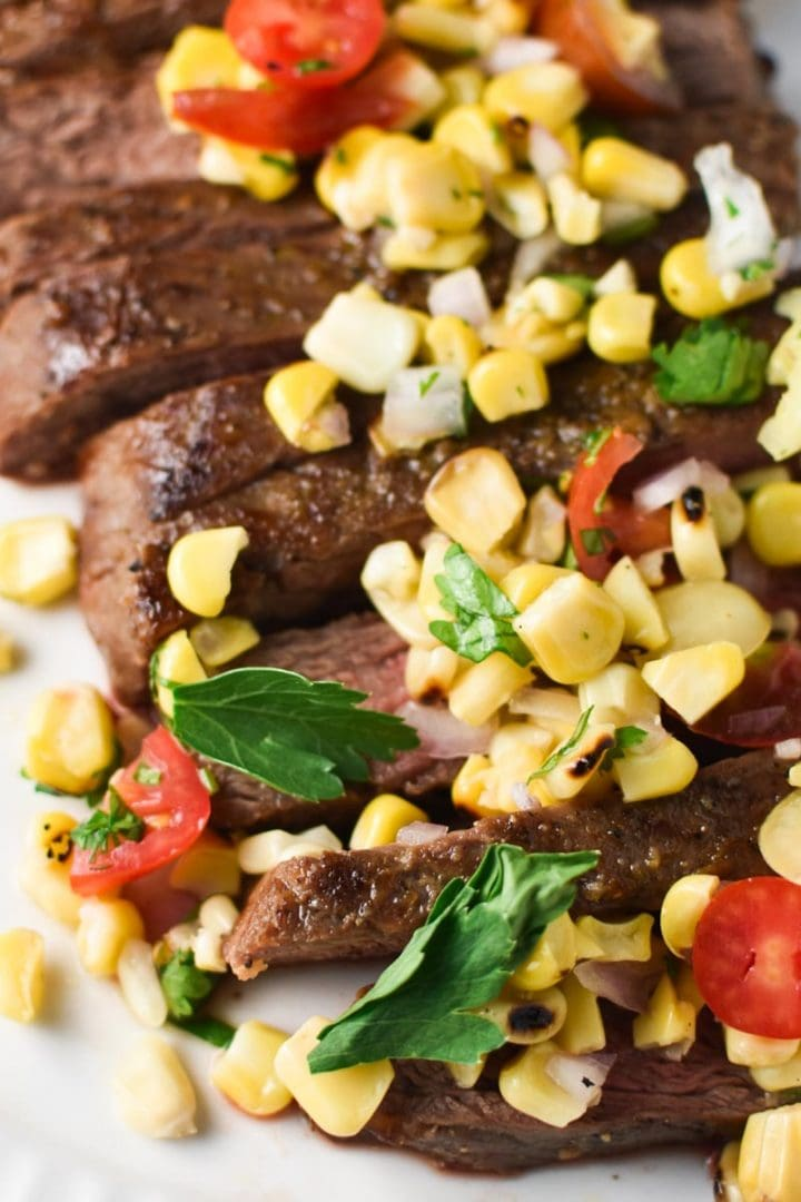 Sliced flank steak on a white plate topped with corn salsa and a fork next to a bowl of corn salsa