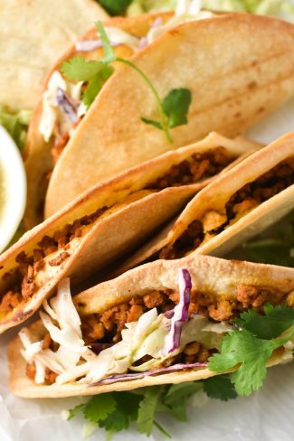 Baked chicken tacos on a white plate with slaw and a bowl of salsa verde