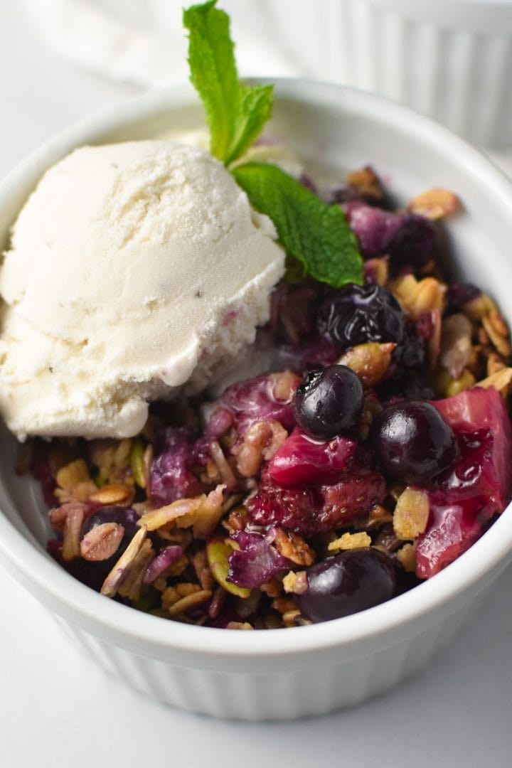A strawberry blueberry crisp topped with oats and vanilla ice cream with a sprig of mint in a white bowl