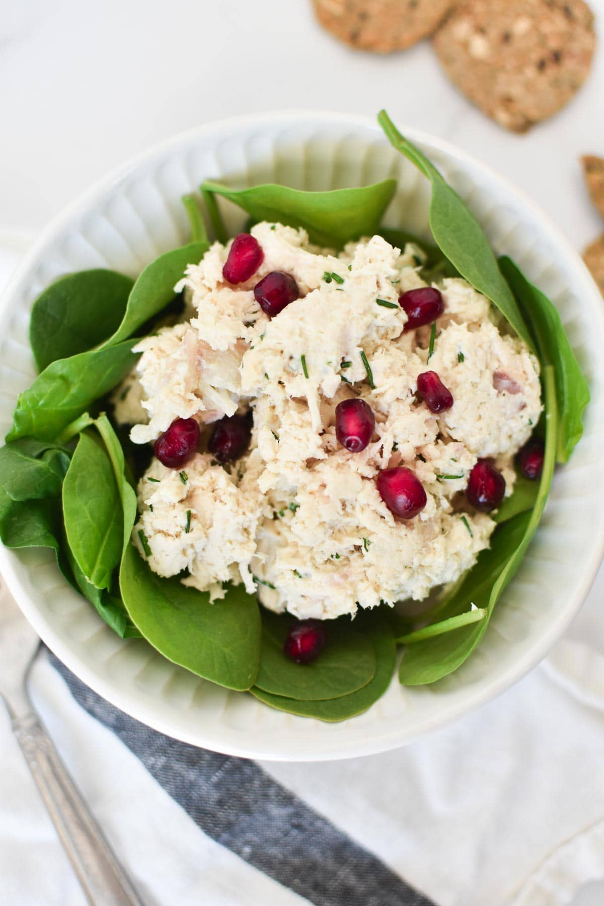 A pomegranate chicken salad in a white bowl next to a fork and crackers
