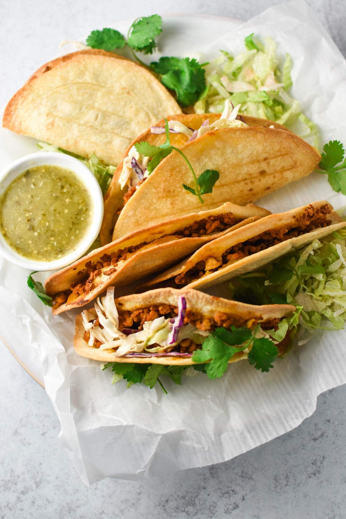 A row of crispy baked tacos on a platter with parchment paper