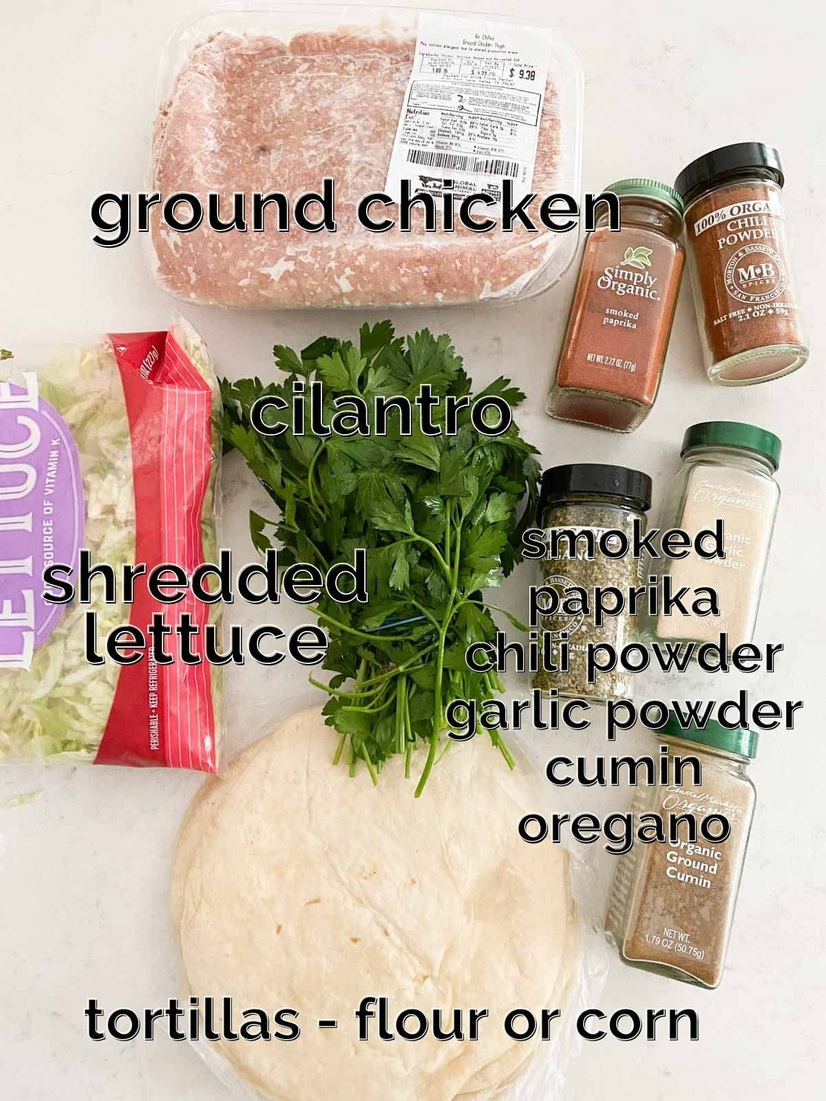 Ground chicken, lettuce, tortillas and spices on a white table