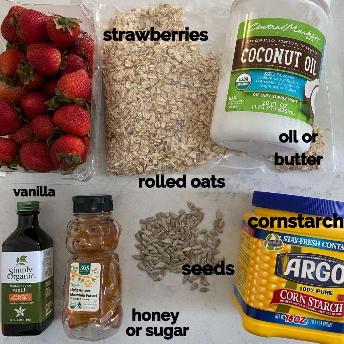 Ingredients for a berry crisp - strawberries, oats, oil, vanilla, sugar, seeds, and cornstarch on a table