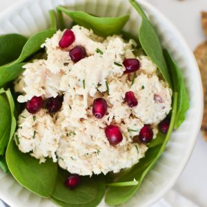 Chicken salad on a bed of spinach greens topped with pomegranate seeds