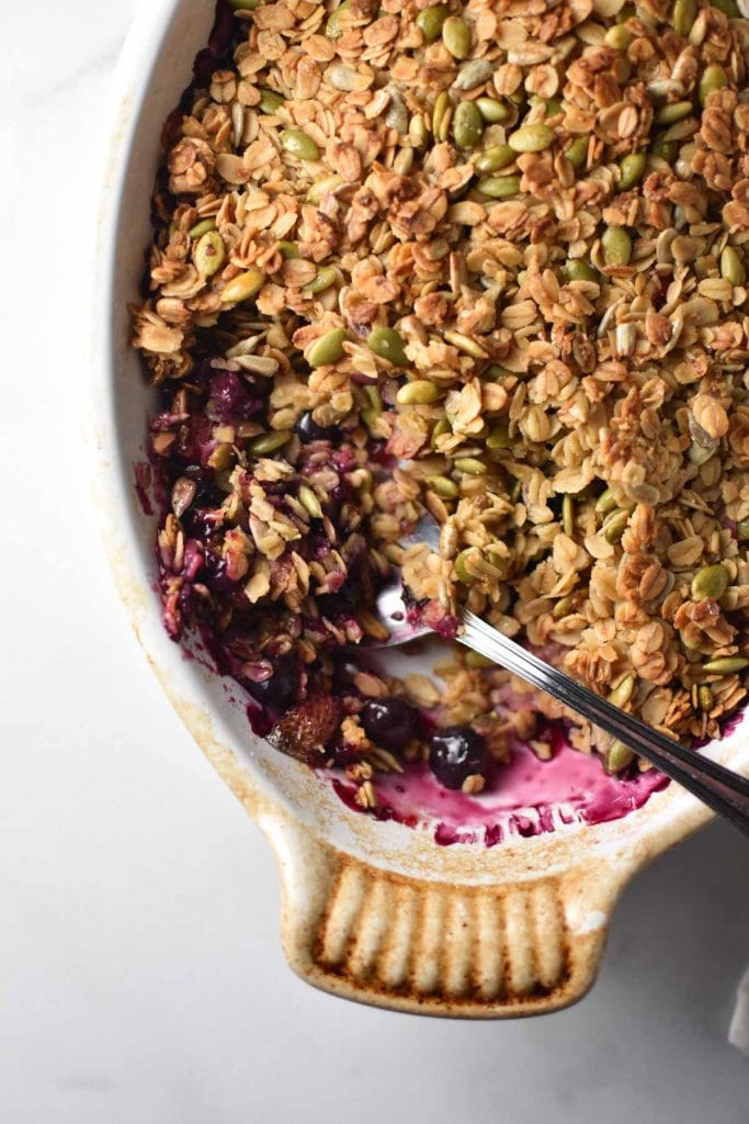 A spoon digging into a gratin dish with a berry crisp topped with seeds and oatmeal