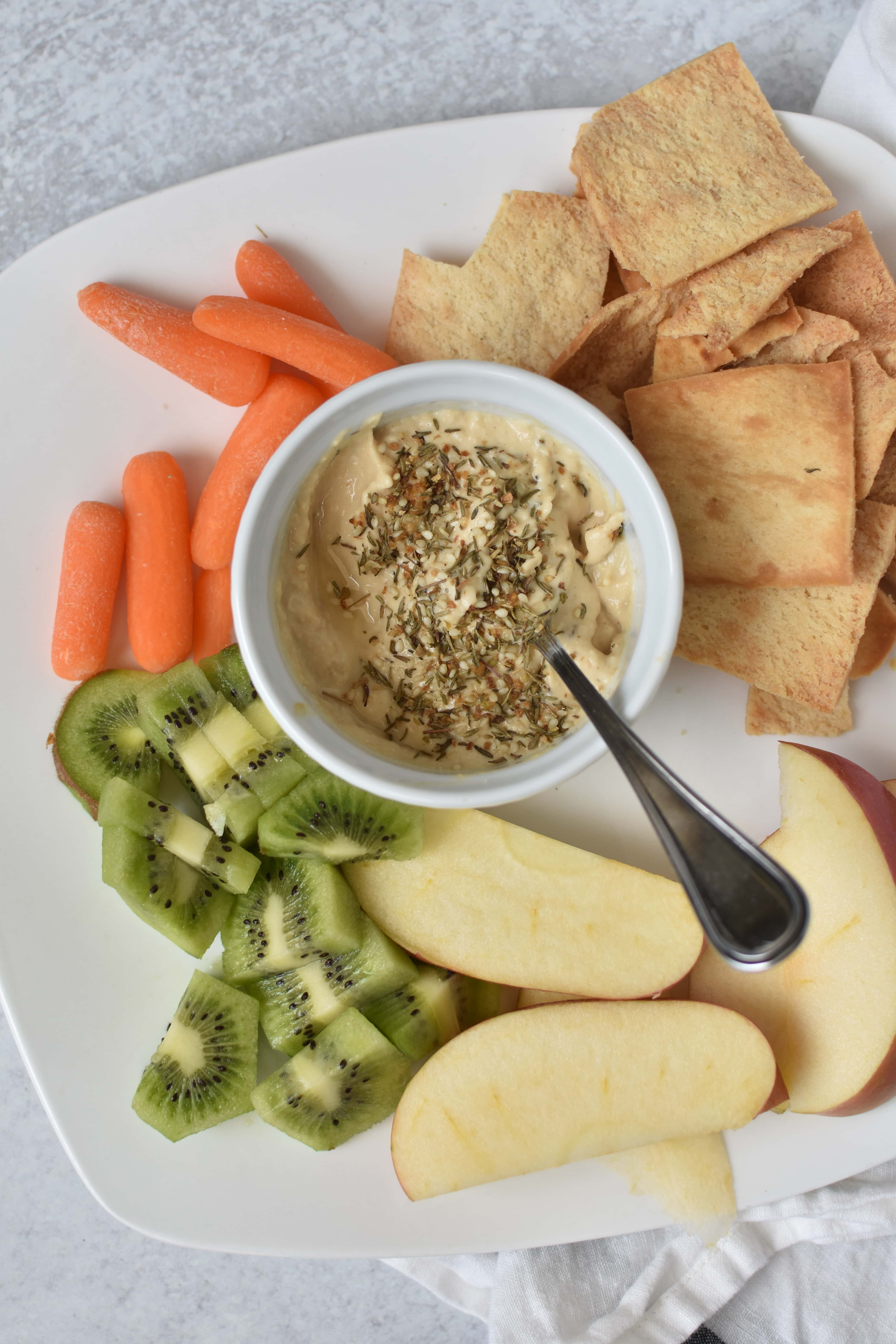 A bowl of hummus with vegetables on a white plate