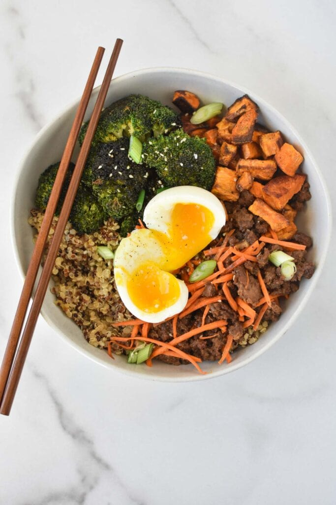 A beef stir fry bowl with a jammy egg on top on a white marble table