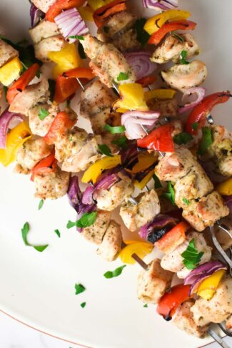 Baked chicken kabobs laid out diagonally on a plate and topped with parsley