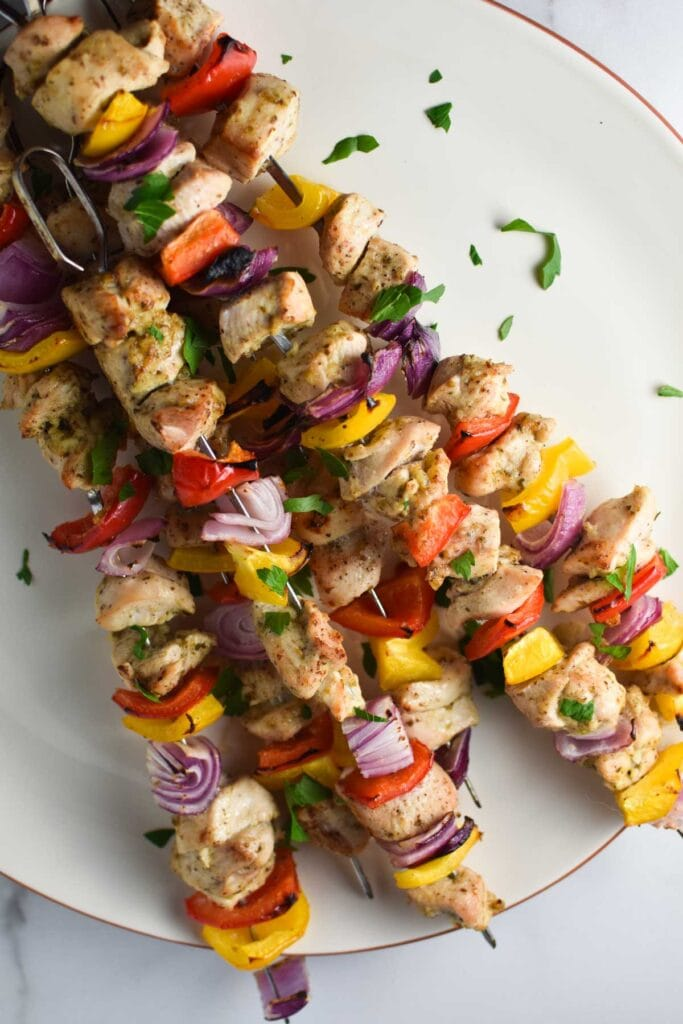 A plate of chicken kabobs stacked on top of each other
