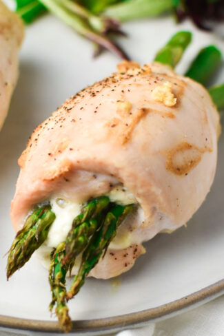 Boursin and asparagus stuffed chicken rolled up on a grey plate with a side salad