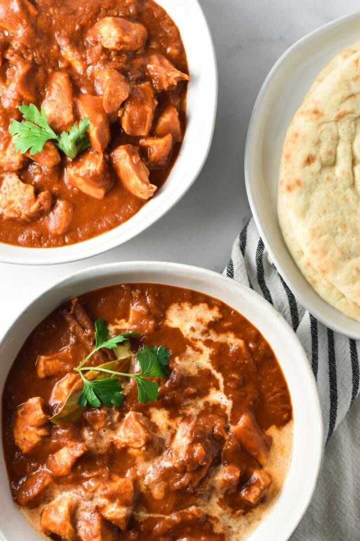 Two bowls of chicken ruby curry, one with cream on top, next to a plate of naan bread and a spoon and fork on a white table