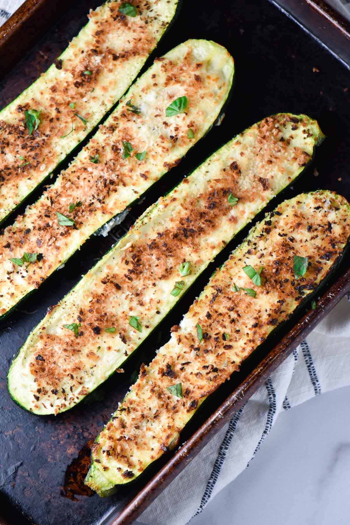 Four zucchini boats with a light brown panko crust on a metal sheet pan and towel